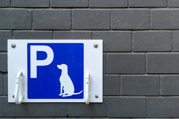 파란색 접시에 지정된 개 주차 기호입니다. 공공 장소 또는 상점에서 가죽 끈을 부착하기 위한 고리가 있는 외부에서 주인을 기다리는 바인드 개를 위한 장소. 공간을 복사합니다. 확대. 옥외.
