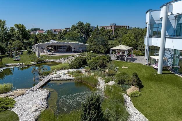 Обустроенный задний двор роскошного особняка с прудом с рыбками в летний день