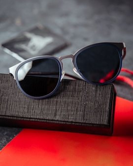 Designed sunglasses on the red book and grey surface