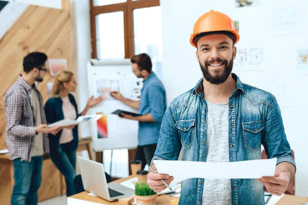 Designer architect is posing with blueprints.
