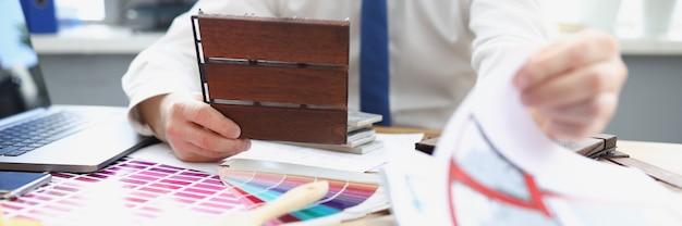 Дизайнер демонстрирует образцы строительных материалов за рабочим столом.