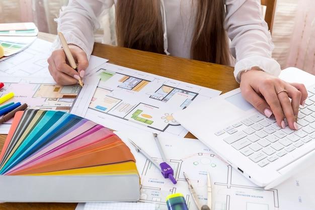 カラーサンプラーとラップトップを使用してハウスプロジェクトを開発するデザイナー