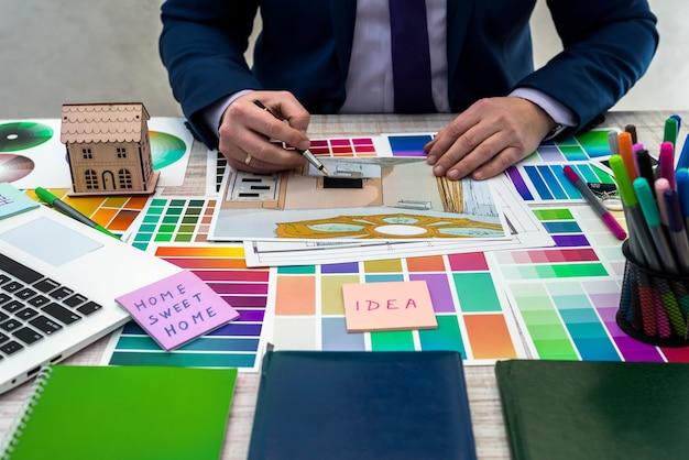デザイナーは、テーブル、オフィスの職場で素材の配色でインテリアイラストのスケッチを開発します。建築家とインテリアデザイナーのデスクトップと機器と材料のサンプル