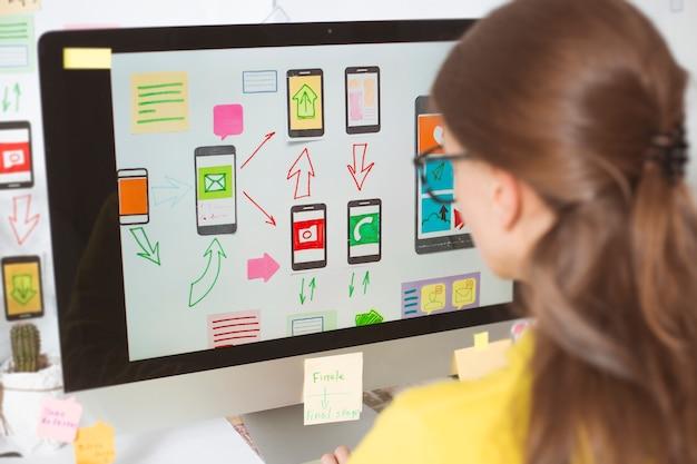Дизайнер разрабатывает приложения для мобильных телефонов.