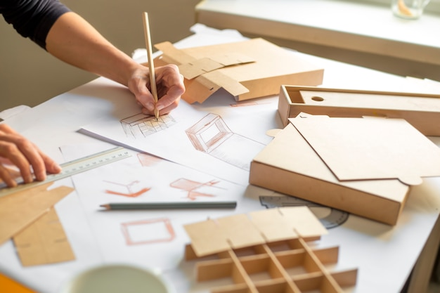 디자이너는 골판지 상자 제작을위한 모형을 그립니다.
