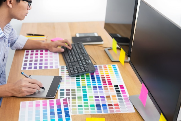 Designer editor at work drawing sketches a new project on graphic tablet and color palette