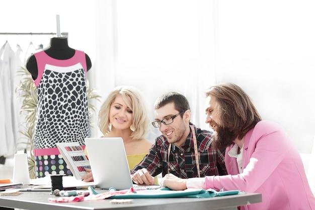 디자이너 그룹은 창의적인 사무실에서 노트북으로 작업합니다.