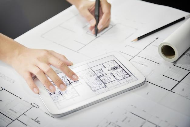 Дизайнерские руки, используя планшет и эскизы.