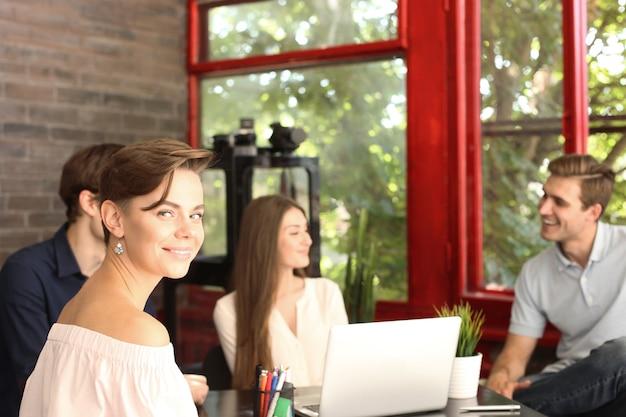 평상복을 입은 디자이너가 앉아 카메라를 보고 웃고 있고, 그의 동료들은 배경에서 일하고 있습니다.