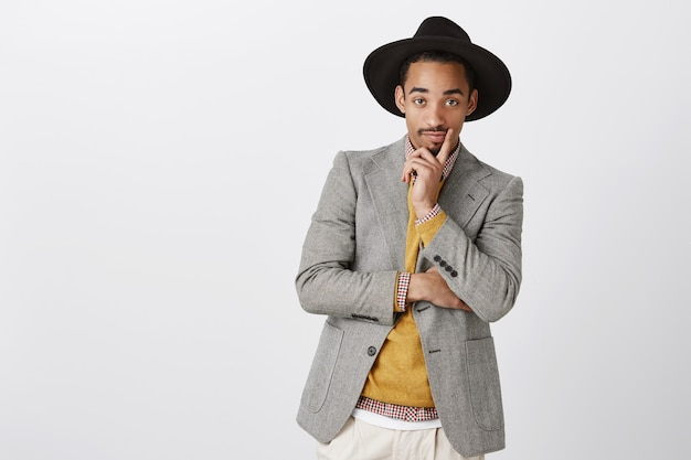 Designer looks at model in his clothes. portrait of classy handsome young man in stylish formal outfit and hat, holding hand on chin, staring curiously, being interested in discussion