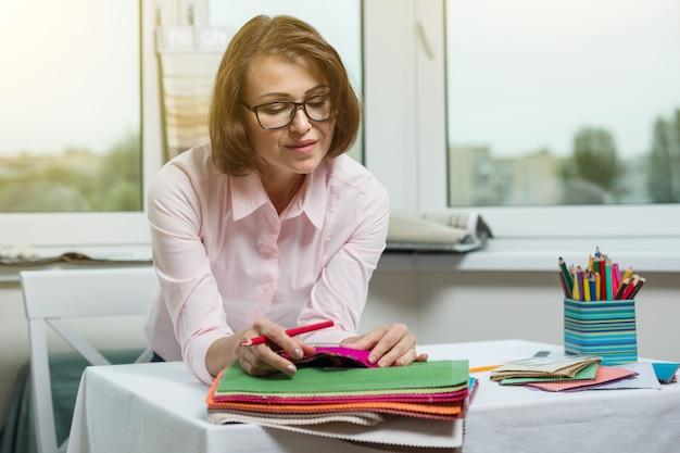 Дизайнер или архитектор позирует и смотрит на тебя, сидя в офисе