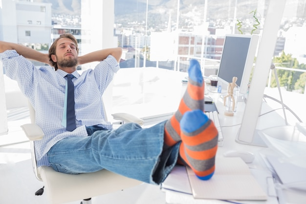 Designer relaxing at desk with no shoes