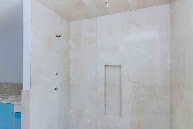 マスターバスルームの壁タイル張りのシャワー付きのデザイナーリフォーム建設バスルーム