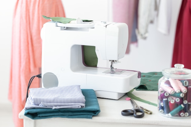 Designer's desk sewing machine thread fabric scissors against the wall of finished stitched products. concept of tailoring to order.