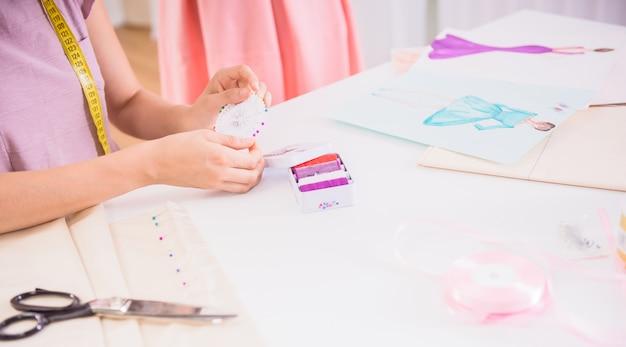 Designer's hands working at new dress in her studio.