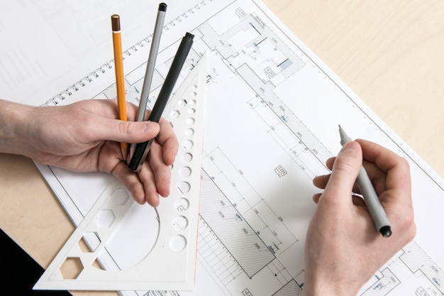 계획에 작업하는 디자이너의 손. 창의적인 예술가 또는 발명가의 직장. 작업 과정을 계속하기 전에 생각을 잠시 멈추십시오.