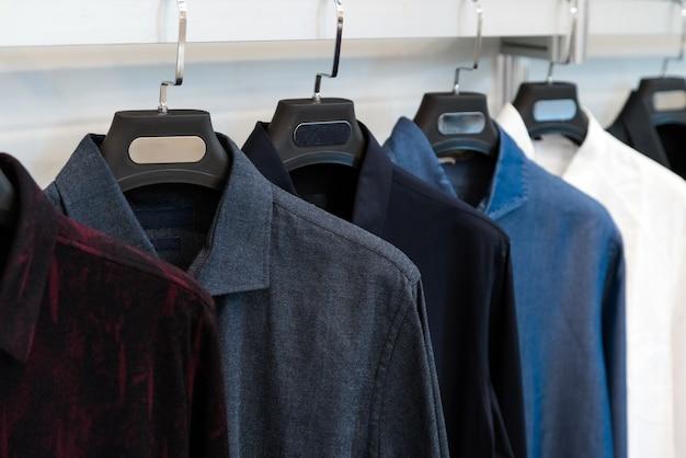 小売店で展示されているデザイナーシャツ、ハンガーにぶら下がっているさまざまな色と質感のシャツ