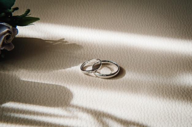 디자이너 실버 두 개의 결혼 반지는 복사 공간이 있는 베이지색 배경에 있습니다. 약혼. 럭셔리 결혼 및 결혼식 개념입니다. 프리미엄 사진