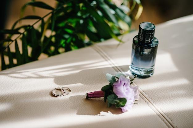 디자이너 실버 2개의 결혼 반지, 향수병, 꽃은 복사 공간이 있는 베이지색 배경에 있습니다. 약혼. 럭셔리 결혼 및 웨딩 액세서리 개념입니다.