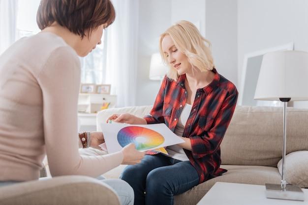 デザイナーソリューション。新しいデザインを選択しながらカラーパレットについて話し合う一緒に座って喜んでポジティブな若い女性