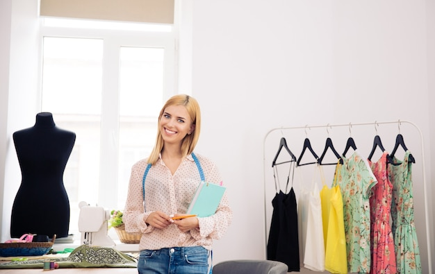 Designer standing in workshop with notebook and pencil