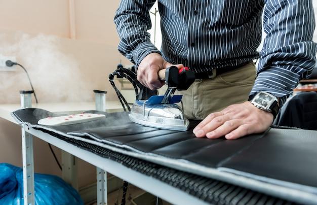 デザイナーのテーラーはシートカバーを縫います。男は仕事に鉄を使う。作業仕立て加工布。繊維工場。