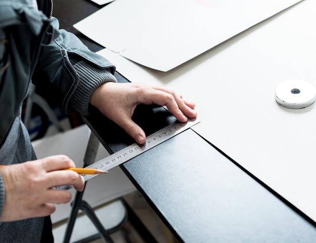 デザイナーのテーラーはシートカバーを縫います。男は彼の仕事にミシンを使用します。