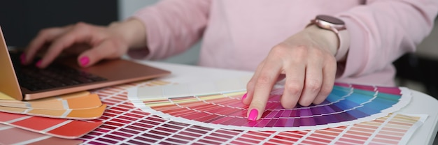 Designer typing on laptop keyboard and choosing color in palette closeup