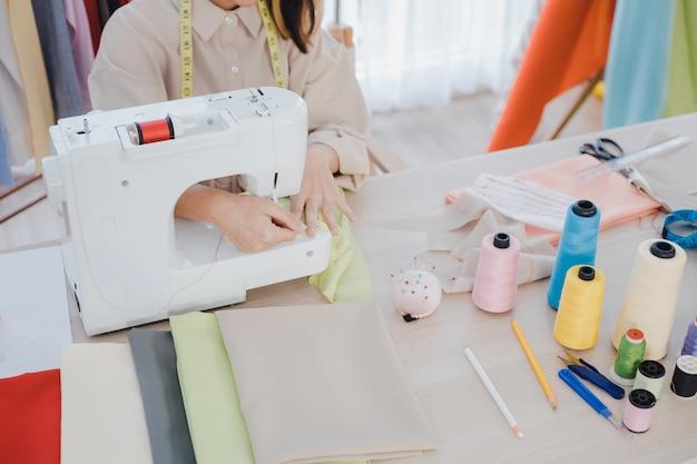 Дизайнер использует швейную машину в работе.