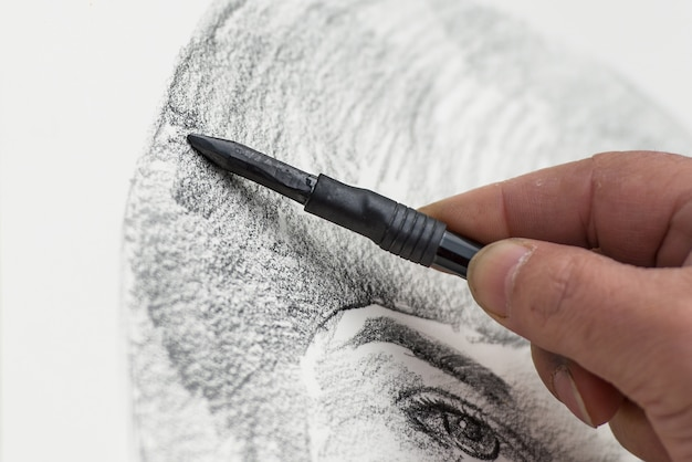 Designer with charcoal drawing a face