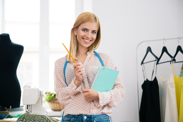 Designer with notebook and pencil standing in workshop