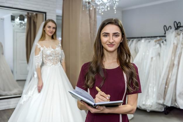 Дизайнер с блокнотом и невеста в свадебном платье сзади