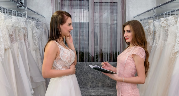 Дизайнер с блокнотом и покупательница в свадебном магазине