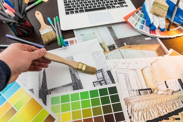 デザイナーは在宅勤務のアパートのスケッチのためのリノベーションの選択色。男はオフィスで家のプロジェクトを描く