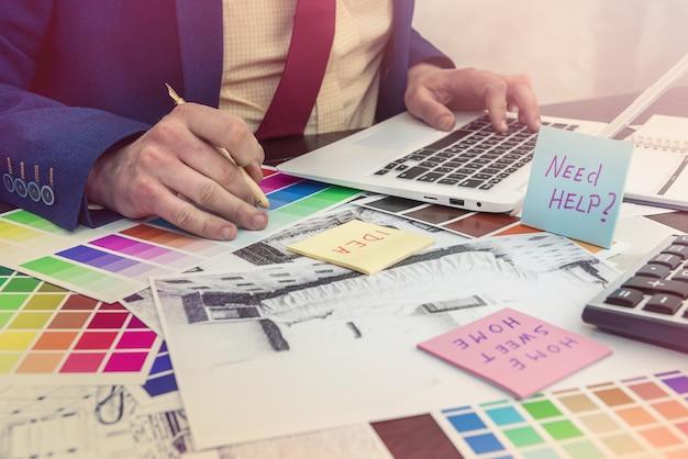 デザイナーは、現代のリフォームのための家の創造的なスケッチとカラーサンプルでオフィスで働きます。建築家プロジェクト