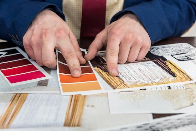 デザイナーは、現代のリフォームのための家の創造的なスケッチとカラーサンプルを使ってオフィスで働きます。建築家プロジェクト