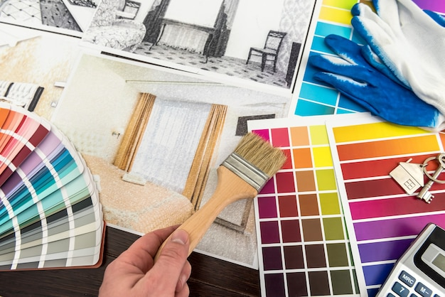 Designer work at home renovation choice color for apartaments sketch. man draw home project at office
