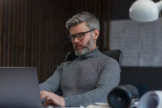 Дизайнер работает в офисе с ноутбуком. архитектор продумывает архитектурный план в поисках новых идей ...