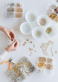 白いテーブルの背景にブライダルアクセサリーを製造、ヘアピースに取り組んでいるデザイナー