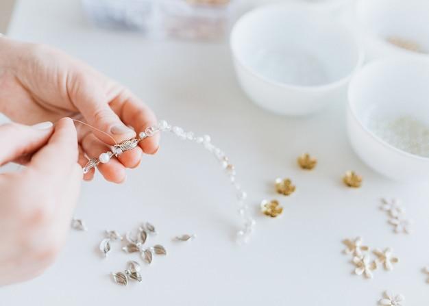 Дизайнер работает над шиньоном, изготавливает свадебные аксессуары на белом фоне стола