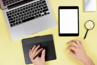黄色の机の上のスタイラスとグラフィックデジタルタブレットに取り組んでいるデザイナー
