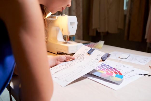 Дизайнер работает над новыми эскизами одежды
