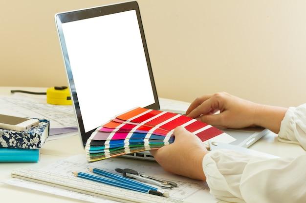 デザイナーの作業テーブル-カラーチャートを保持しているデザイナーの手、空の画面上のスペースをコピー