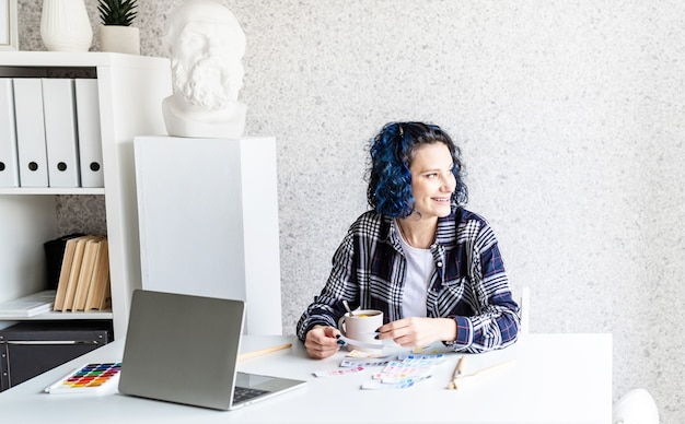 アートスタジオでカラーパレットとラップトップを扱うデザイナー