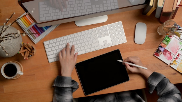 Дизайнер, работающий с цифровым планшетом и компьютером на деревянном офисном столе с дизайнерскими принадлежностями