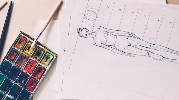 Рабочее место дизайнера. эскизы моды. рисунок женской модели. кисть палитры на столе.
