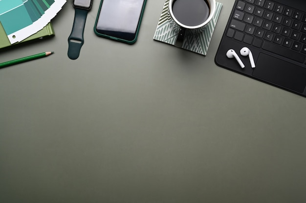 Designer workplace with smart watch, mobile phone , keyboard, color swatches on green table.