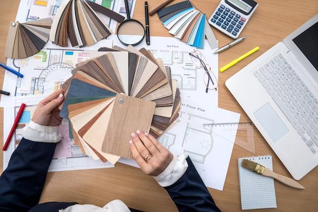 デザイナーは、色のサンプル、ラップトップ、建物の計画を使ってオフィスで働いています