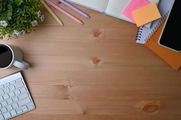 Дизайнерское рабочее пространство с мобильным pone, запиской, комнатным растением, кофейной чашкой и клавиатурой на деревянном столе.