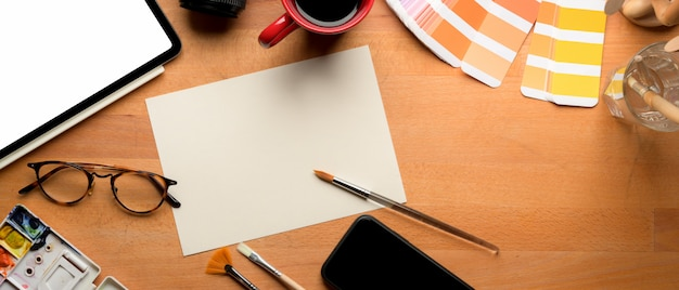 Designer workspace with mock-up sketch paper, tablet and painting tools